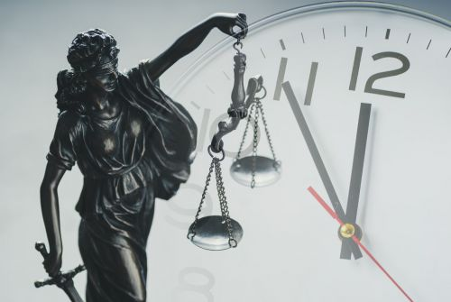 Lady Justice in front of a clock