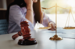 woman on phone behind gavel and scales of justice